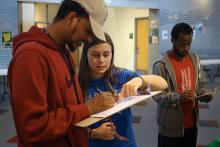 Student with clipboard filling out their registration while another student helps
