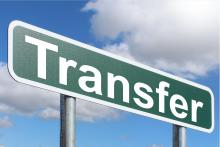 "Image of a green street sign that says ""Transfer"" in front of a blue sky with clouds."