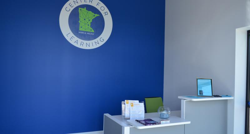 Front desk against blue wall with Center logo featured on the wall