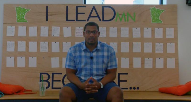2017-18 President Isaac Jahraus sitting in front of I LeadMN Because... board